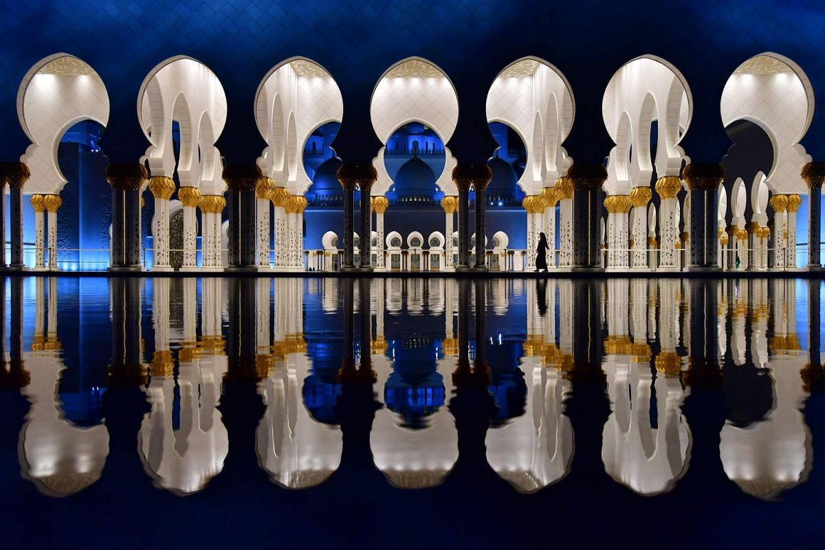 A picture taken on December 3, 2017 shows visitors walking in the courtyard of the Sheikh Zayed Grand Mosque in the UAE capital Abu Dhabi. PHOTO: AFP