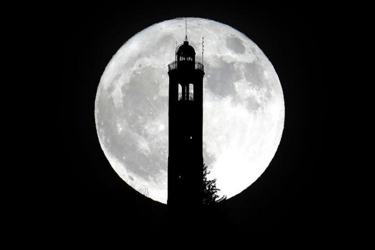 The supermoon above the lighthouse of San Maurizio in Brunate, near Como, Italy.