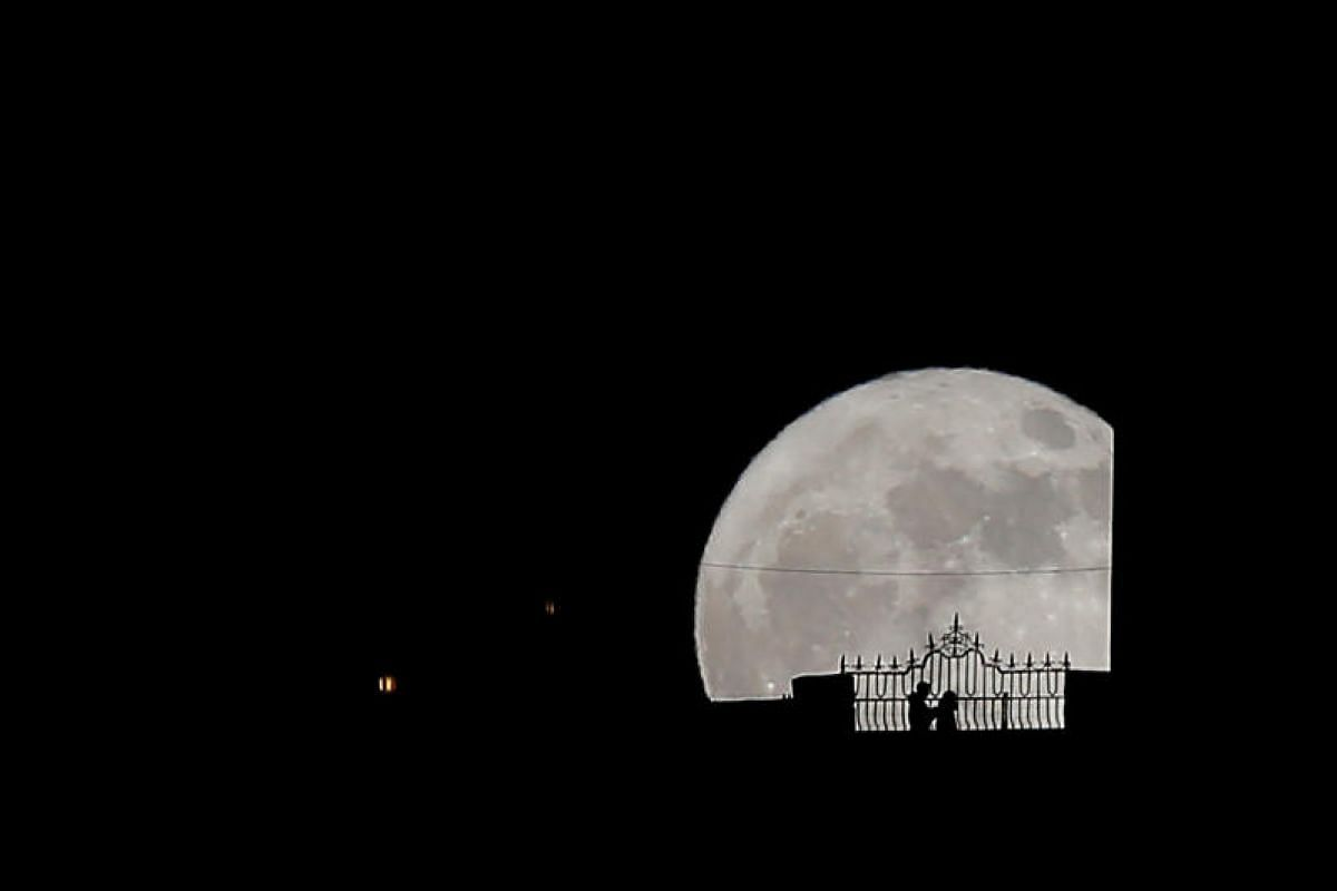 People walk along the Puente Nuevo (New Bridge) silhouetted against the supermoon in Ronda, southern Spain.