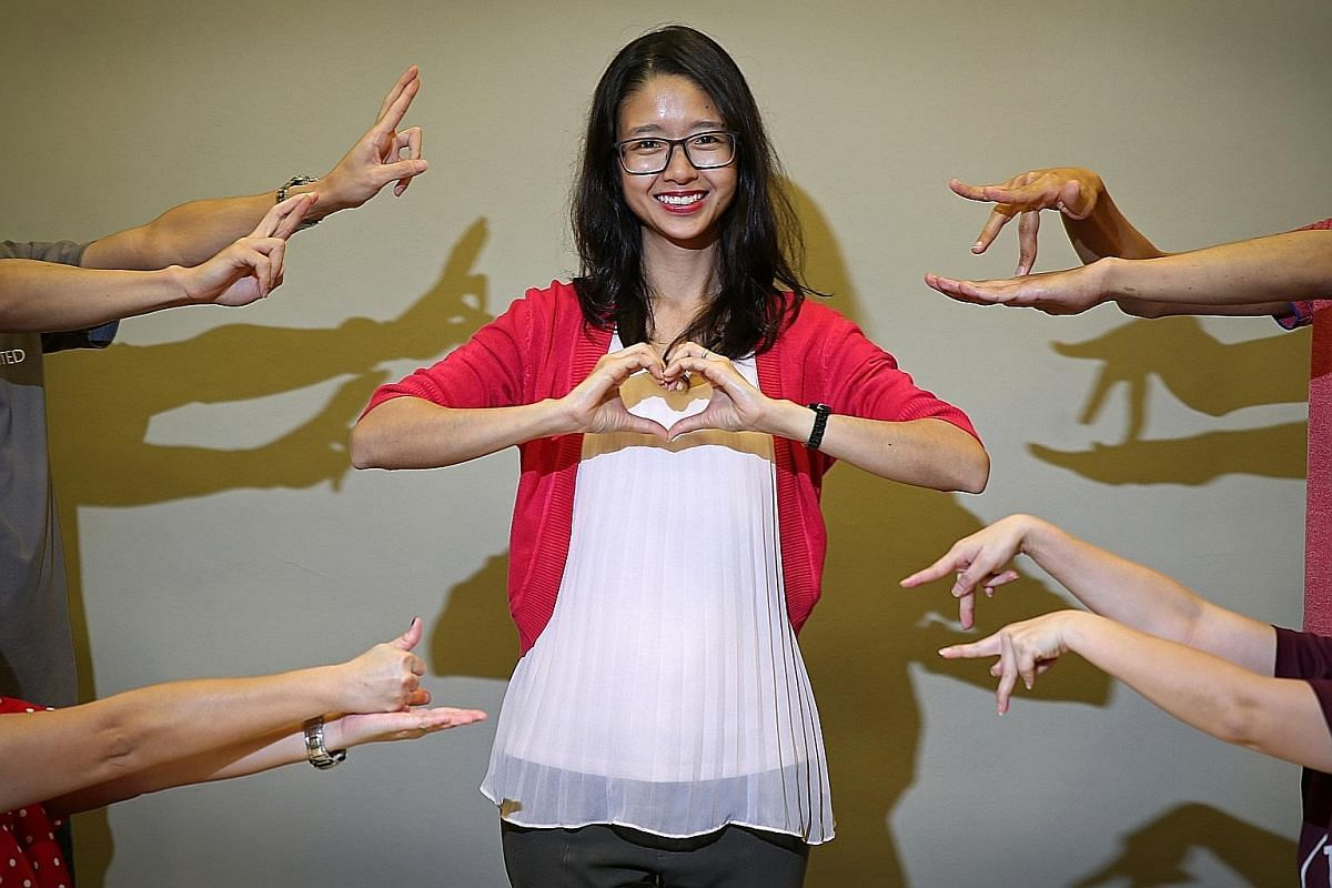 """Ms Charlene Wong, who was born deaf, with volunteers who are signing the words (clockwise, from bottom left) """"help"""", """"hope"""", """"touch"""" and """"people"""". Her work as a community outreach executive includes building volunteers' confidence."""