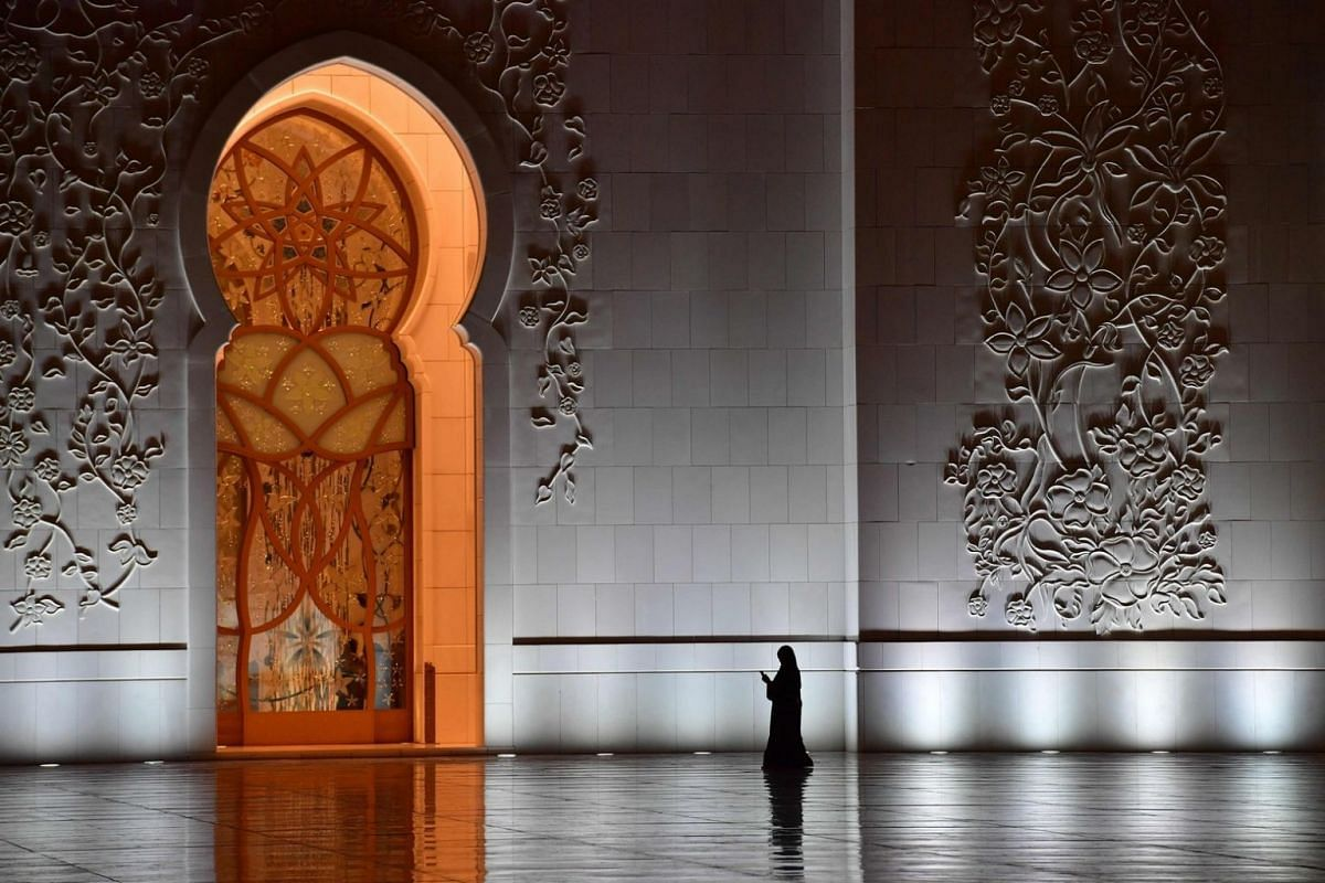 A visitor walking in the courtyard of the Sheikh Zayed Grand Mosque.