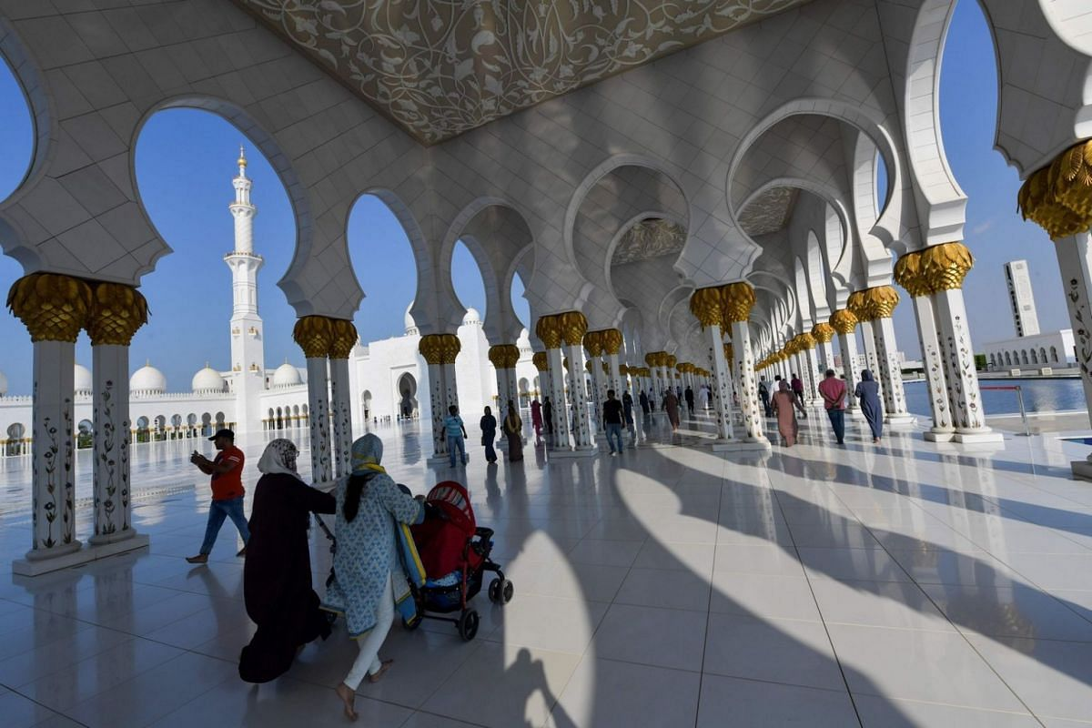 Visitors walking in the courtyard of the Sheikh Zayed Grand Mosque.