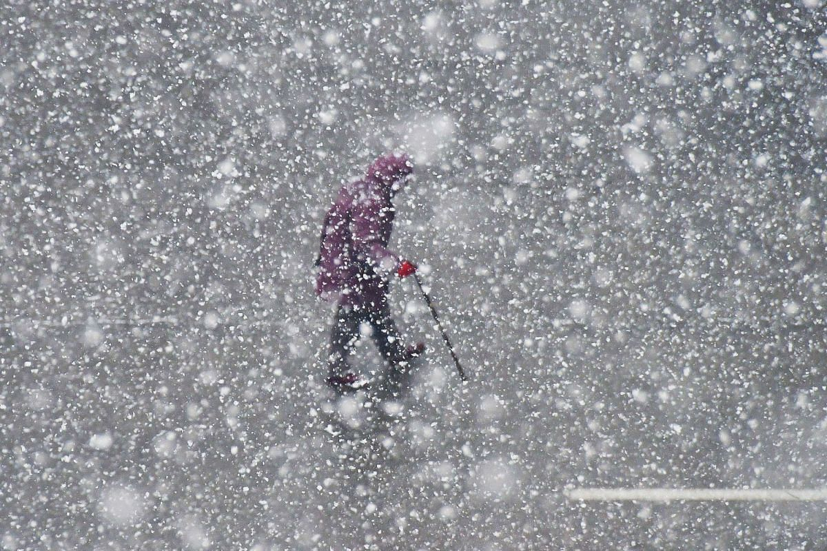 A resident walks during a snowfall in Yantai in China's eastern Shandong province on December 4, 2017. PHOTO: AFP