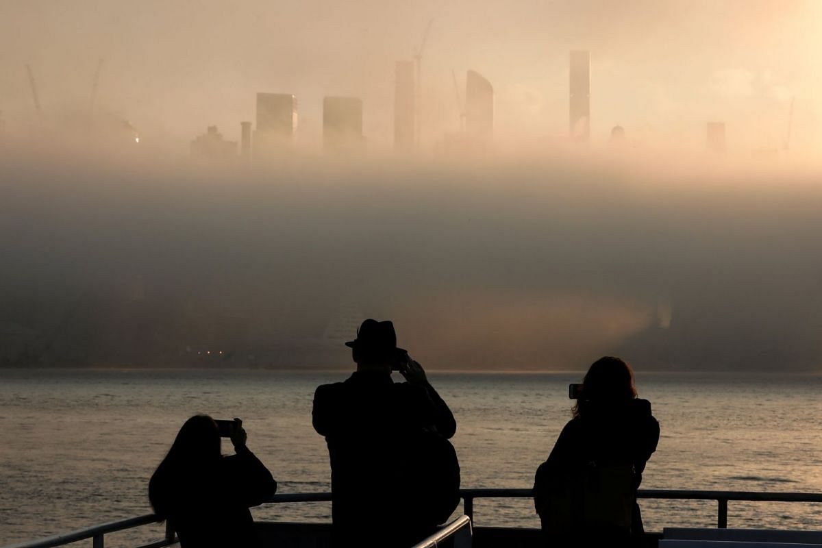 Commuters on a Hudson River ferry photograph the fog-shrouded skyline of New York City, as the sun rises in New York, U.S., December 4, 2017. PHOTO: REUTERS