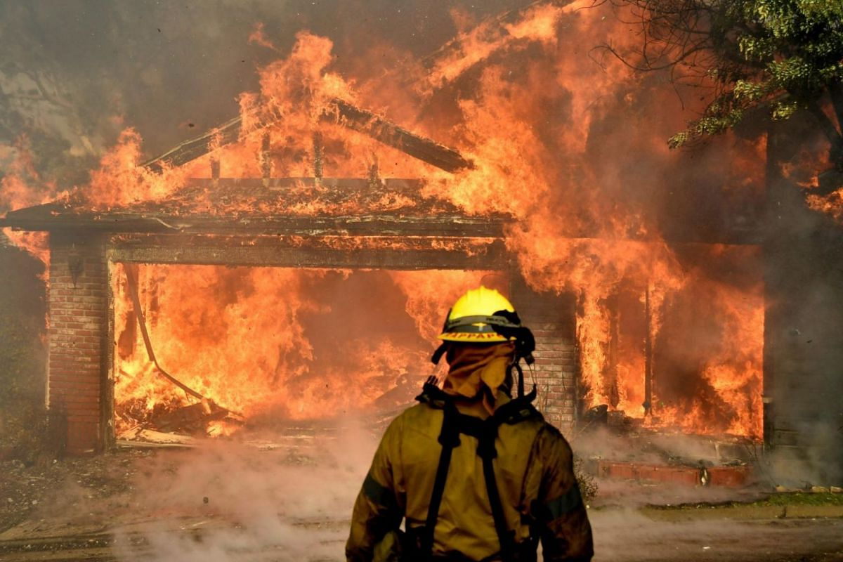 Firefighters battle to save one of many homes burning in an early-morning creek fire that broke out in the Kagel Canyon area in the San Fernando Valley.