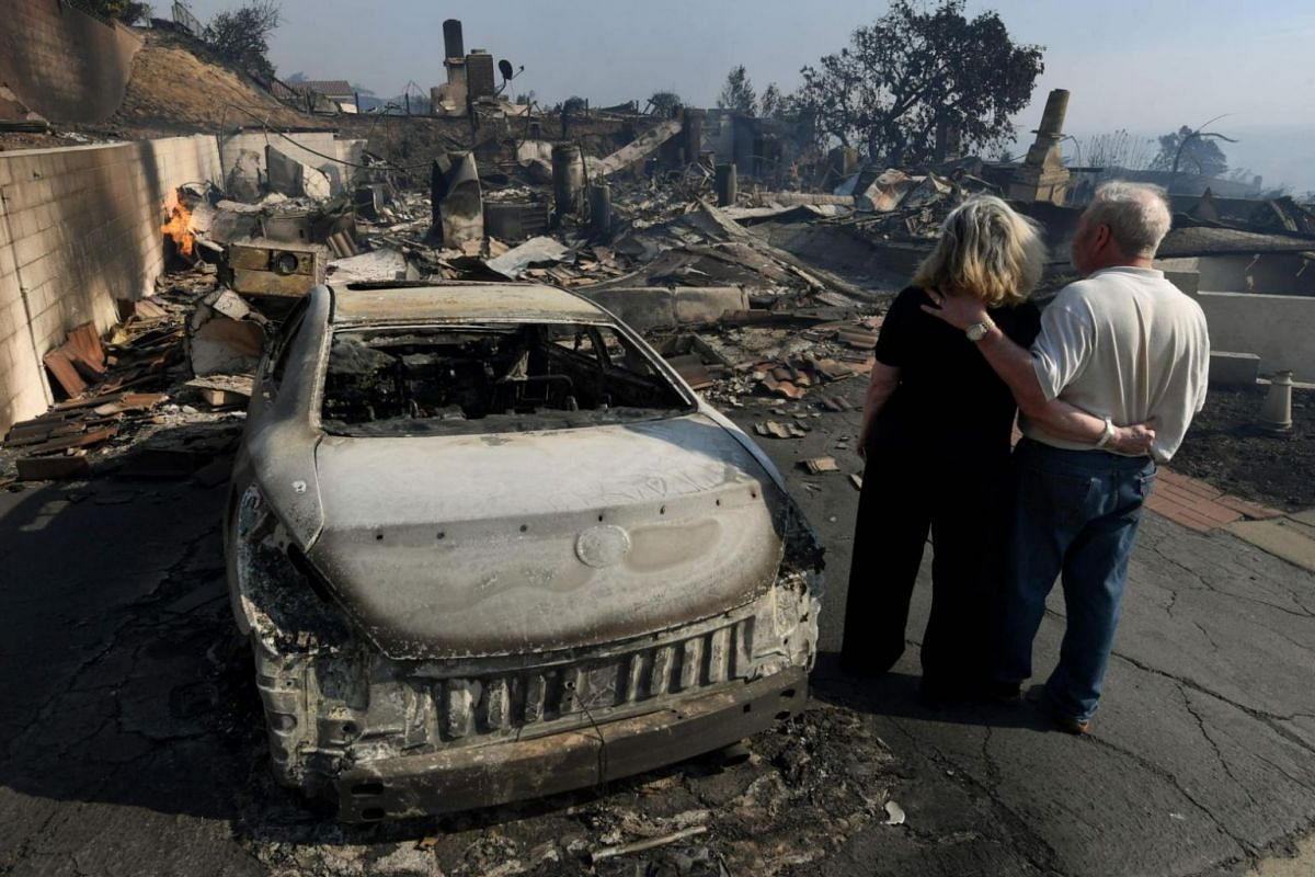 Michael and Vonea McQuillam stand beside their house that was burnt to the ground during the Thomas wildfire in Ventura, California.