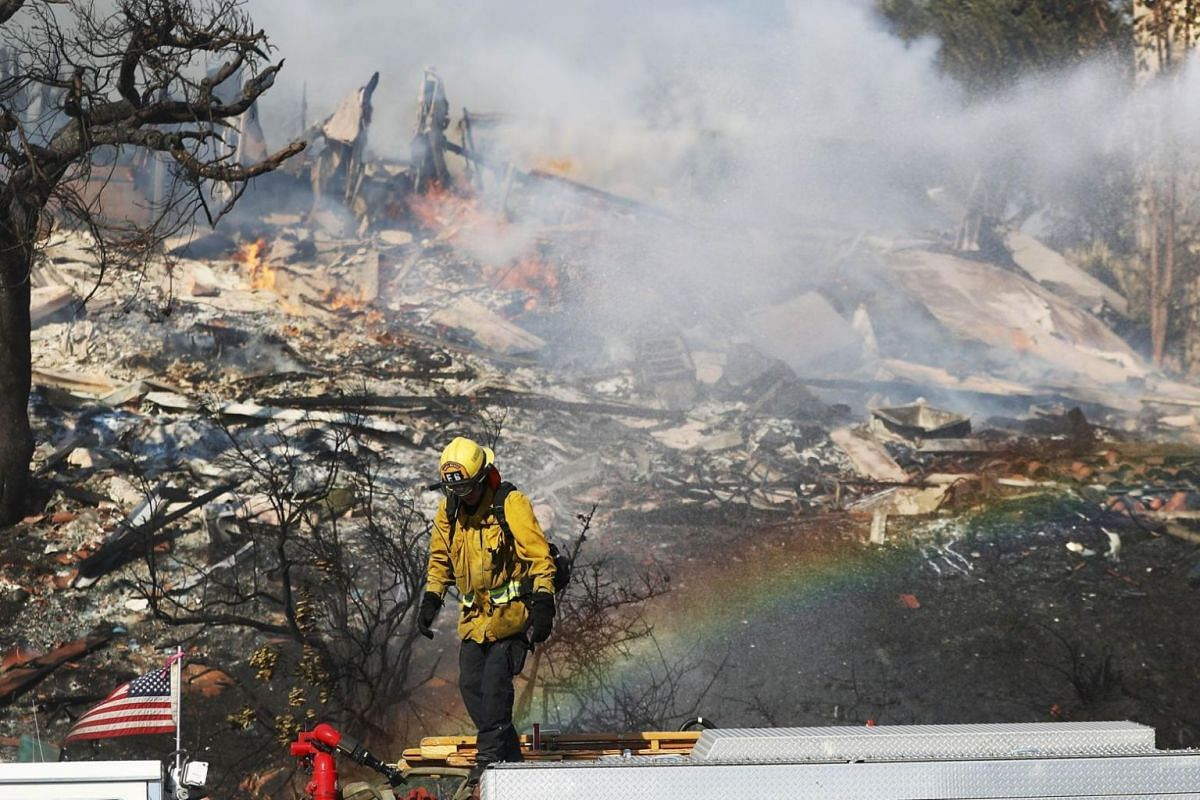 A firefighter battling flames from the Thomas Fire in a residential neighbourhood.
