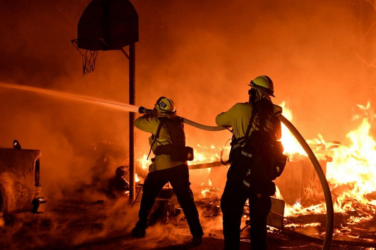 Firefighters battle flames from a Santa Ana wind-driven fire.