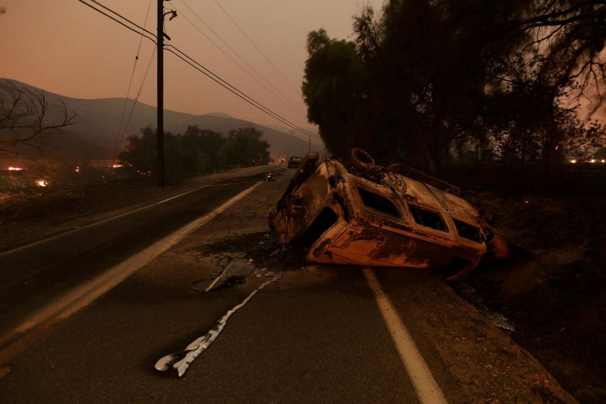 The burned remains of crashed cars are seen at night on a country road as strong winds push the Thomas Fire across thousands of acres.