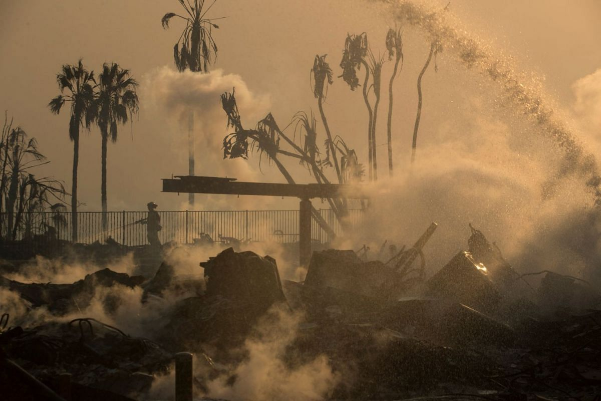 A firefighter sprays water on the remains of the Hawaiian Village apartments after a wind-driven wildfire swept into the city of Ventura, California, U.S., Dec 5, 2017. PHOTO: REUTERS