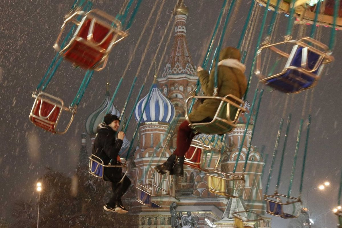 Youths ride a carousel in front of St. Basil's Cathedral in Red Square in Moscow, Russia on Dec 5, 2017. PHOTO: REUTERS