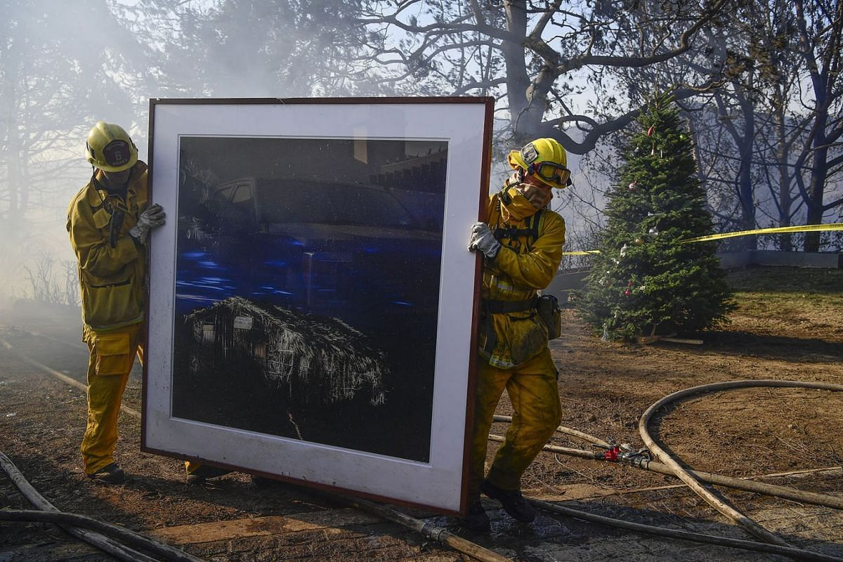 Firefighters remove a painting as they continue to extinguish fires in a home during the 'Skirball Fire' which began early morning in Bel-Air, California, USA, Dec 6, 2017. PHOTO: EPA-EFE