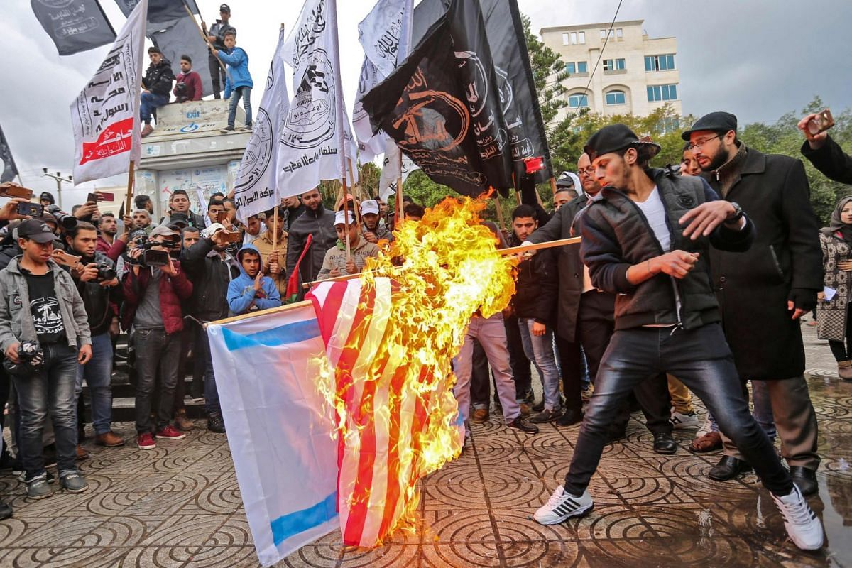 Palestinian protesters burn the US and Israeli flags in Gaza City on Dec 6, 2017. PHOTO: AFP