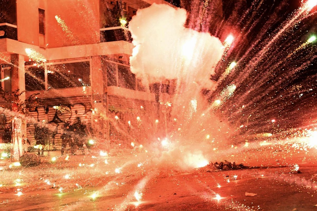 A firework explodes at riot police during clashes with protesters in central Athens on Dec 6, 2017, after a demonstration commemorating 15-year-old Alexis Grigoropoulos, who was fatally shot by a police officer in 2008. PHOTO: AFP