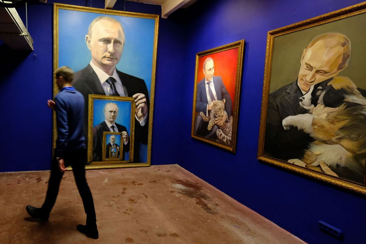 """A man walks past paintings depicting Russian president Vladimir Putin at the """"SUPERPUTIN"""" exhibition at UMAM museum in Moscow on Dec 6, 2017. PHOTO: AFP"""
