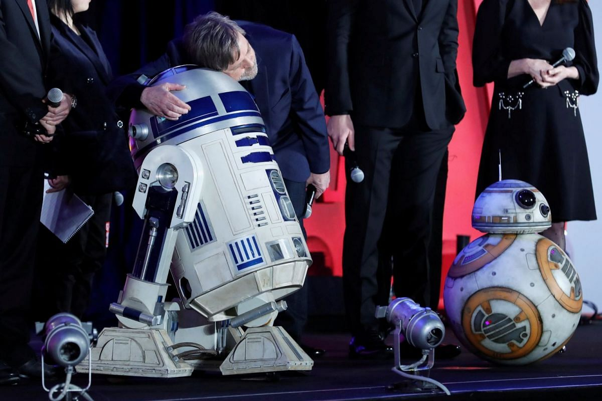 """Cast member of the movie """"Star Wars: The Last Jedi"""" Mark Hamill hugs Star Wars character R2-D2 at its promotional event in Tokyo, Japan on Dec 6, 2017. PHOTO: REUTERS"""
