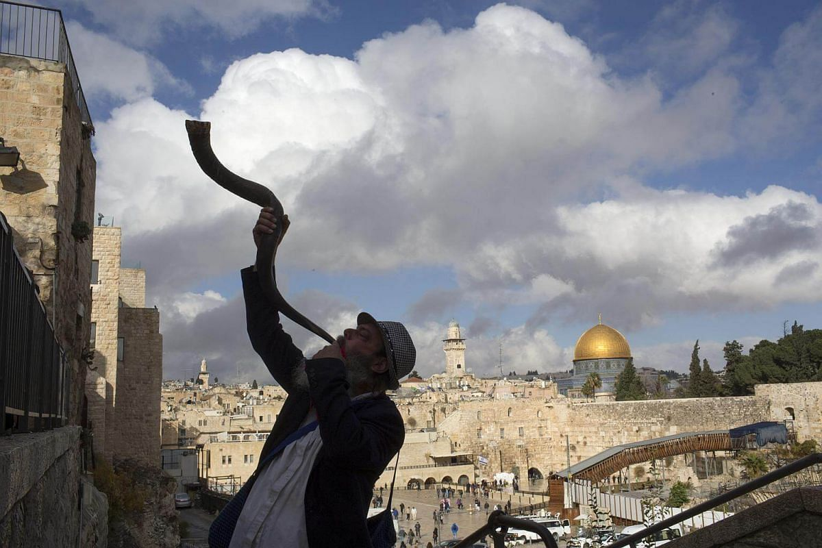 A Jewish man blows a shofar with the Dome of the Rock in the distance, in Jerusalem, on Dec 6, 2017.