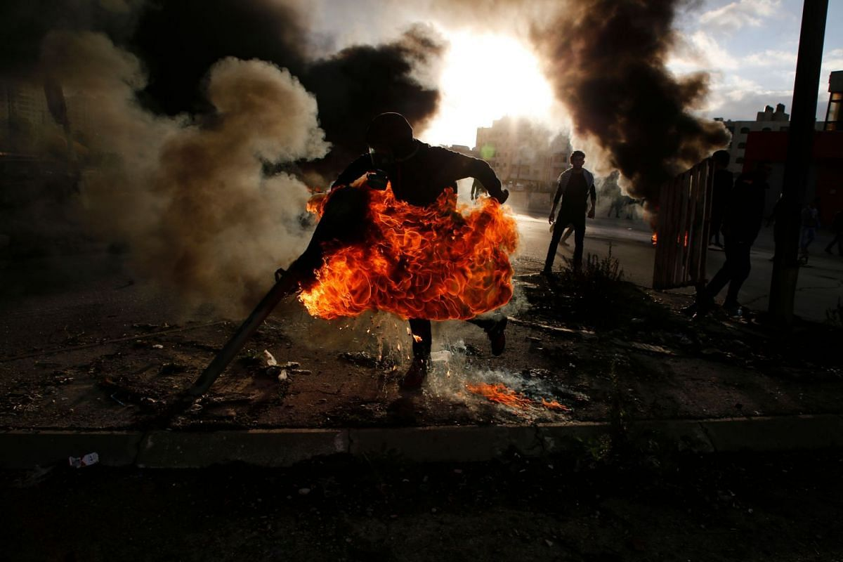 A Palestinian protester runs after catching fire during clashes with Israeli troops at a protest against US President Donald Trump's decision to recognise Jerusalem as the capital of Israel, near the Jewish settlement of Beit El, near the West Bank c