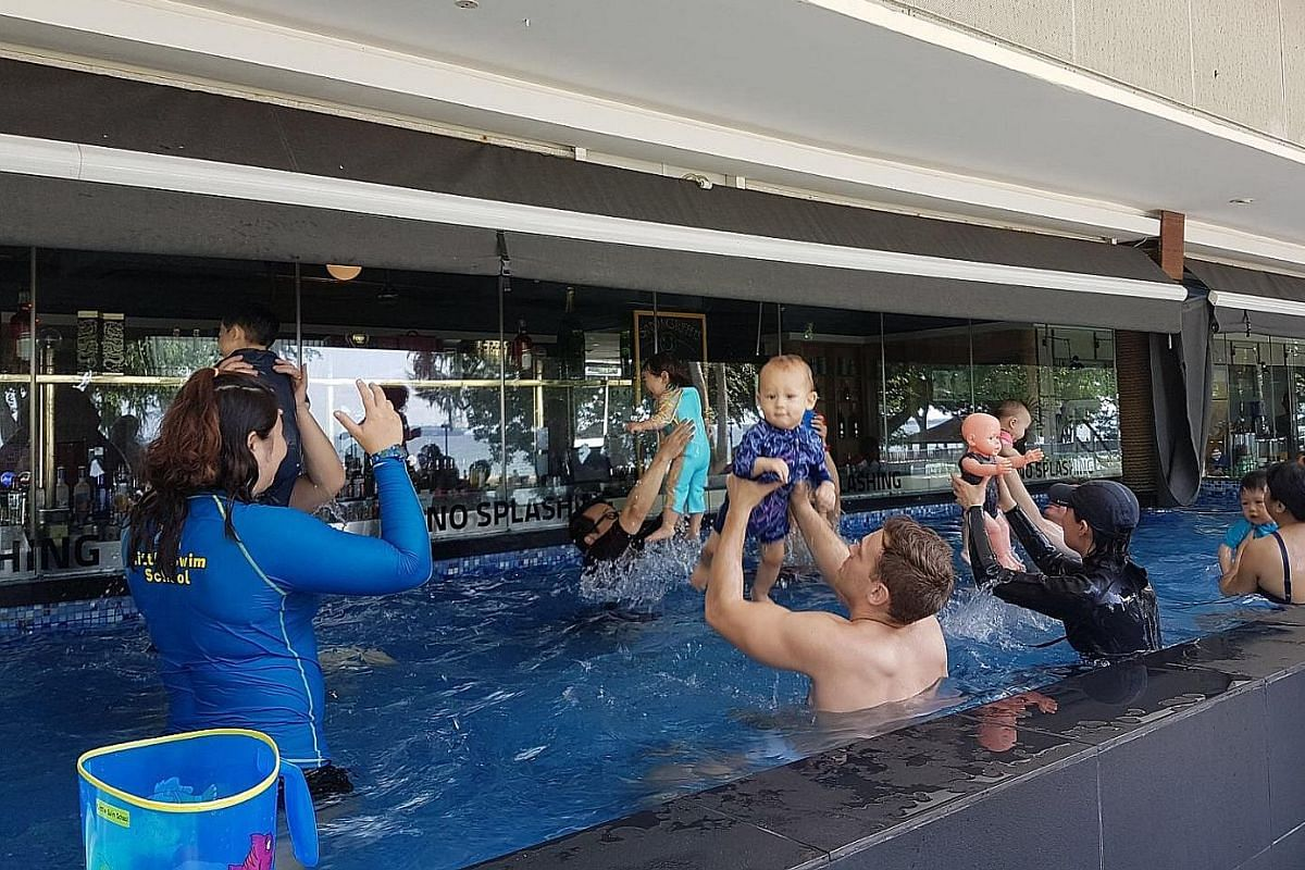 Parents and their children at a swimming lesson at the SandBank restaurant, which has a 15m-long sheltered and temperature-regulated plunge pool.