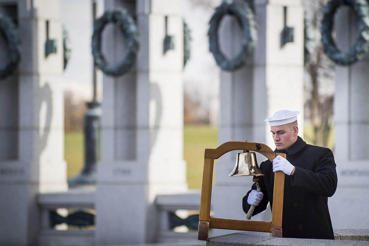A serviceman with the US Navy rings a ship's bell to mark the time of the Japanese attack on Pearl Harbor during the Friends of the National World War II Memorial and the National Park Service to commemorate Pearl Harbor Remembrance Day in Washington