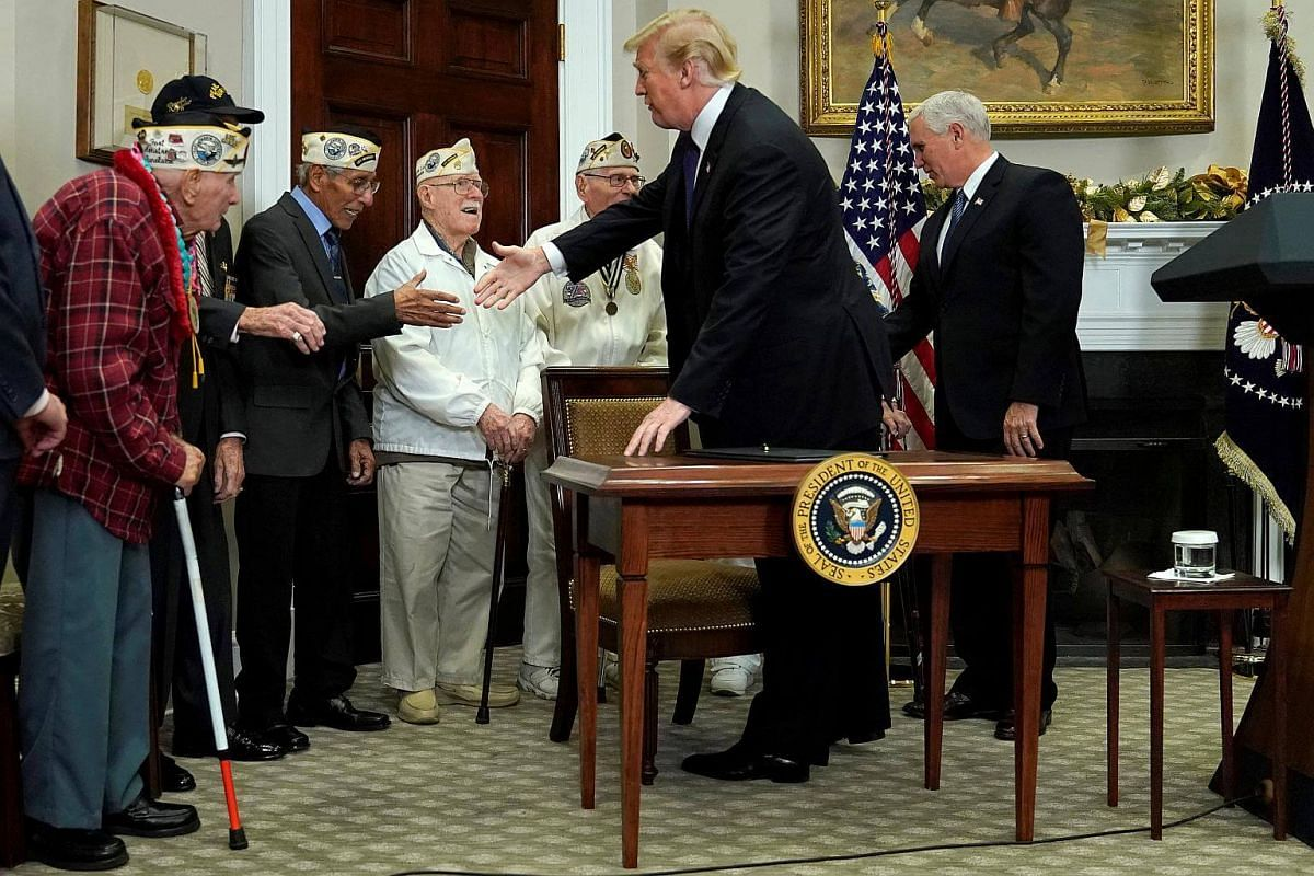 US President Donald Trump greets Pearl Harbor veterans during a proclamation ceremony for National Pearl Harbor Day in the Roosevelt Room at the White House in Washington, on Dec 7, 2017.