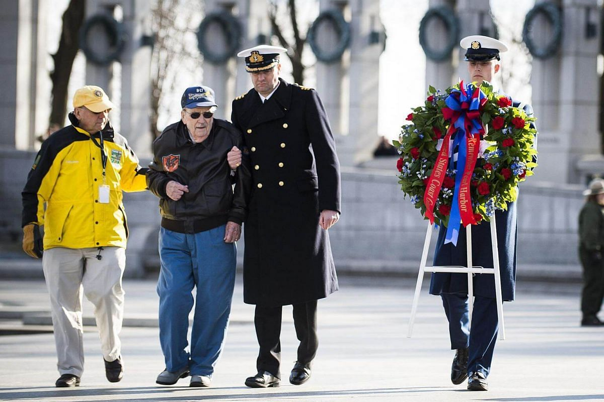 A National Park Service volunteer escorts Retired Air Force Staff Sgt. Bill Hare, 91, as he places a wreath during a ceremony held by the Friends of the National World War II Memorial and the National Park Service to commemorate Pearl Harbor Remembra