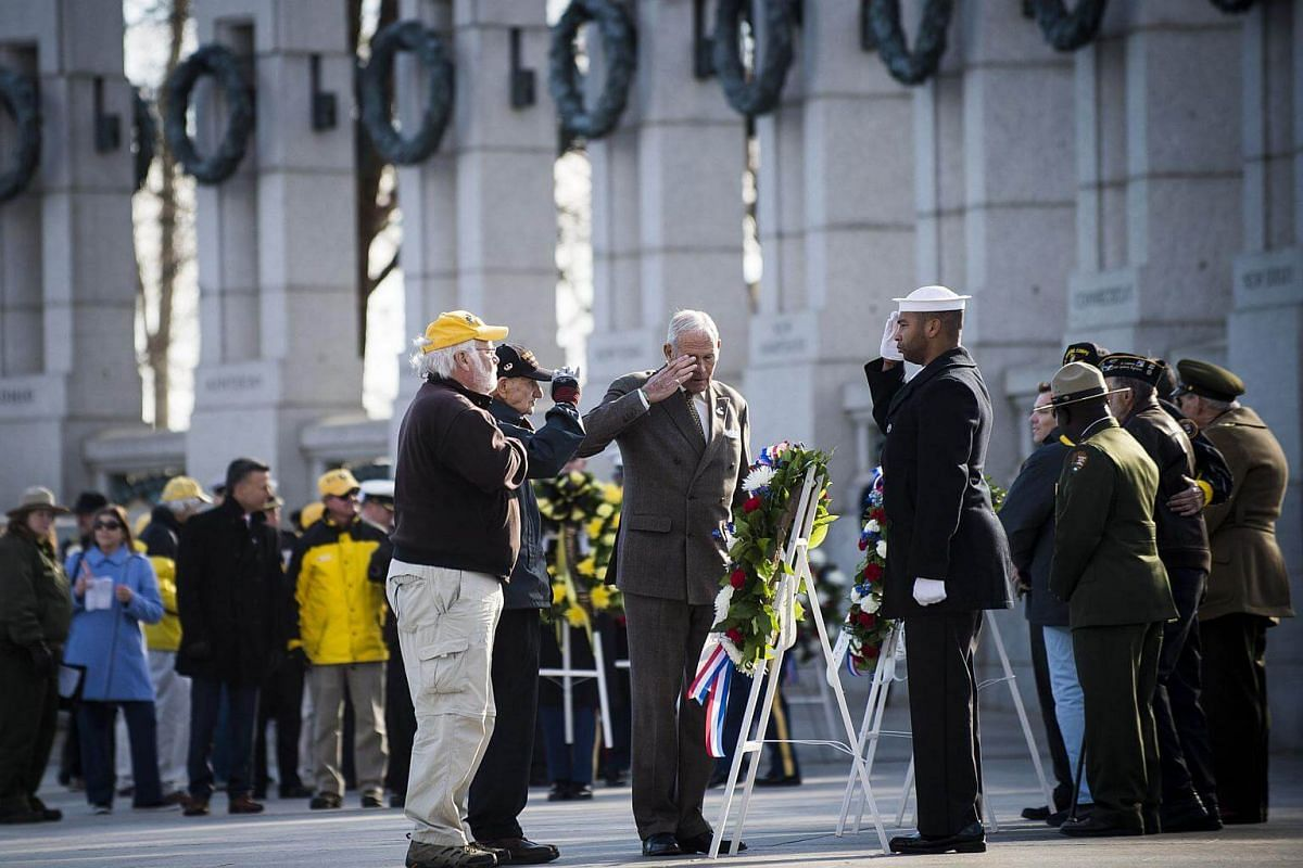 A National Park Service volunteer escorts Retired Army Master Sgt. Norman Duncan, as he places a wreath during a ceremony held by the Friends of the National World War II Memorial and the National Park Service to commemorate Pearl Harbor Remembrance