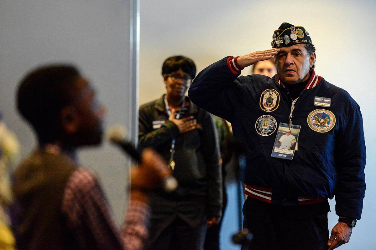 A man salutes during a wreath-laying ceremony aboard the Intrepid Sea, Air and Space Museum in New York City, on Dec 7, 2017.