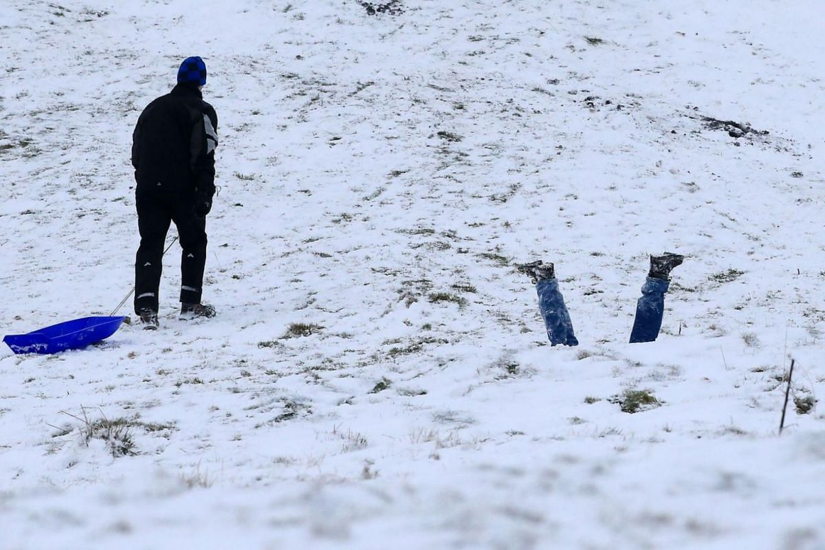 Pedestrians walk as snow falls over central London on Dec 10.