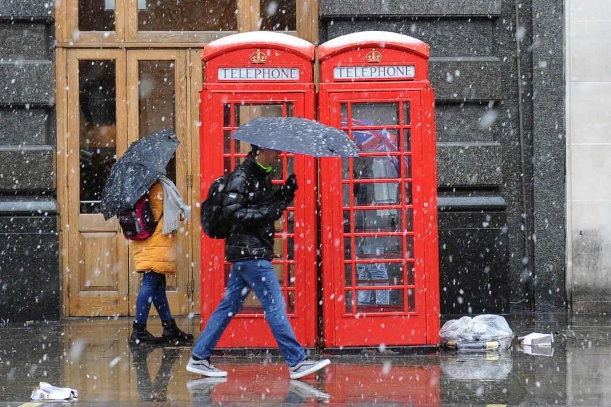Pedestrians walk by a telephone booth as snow falls over central London.