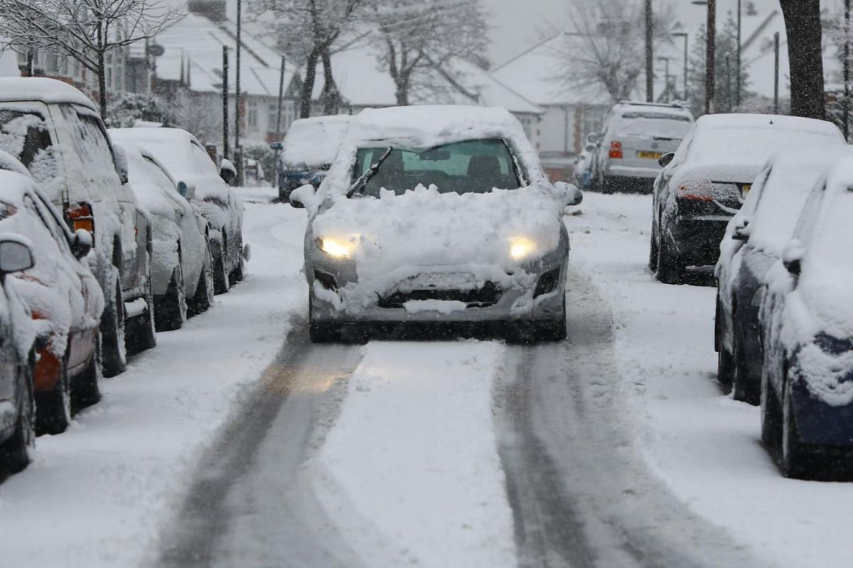 A motorist drives along a snowy road in north London.