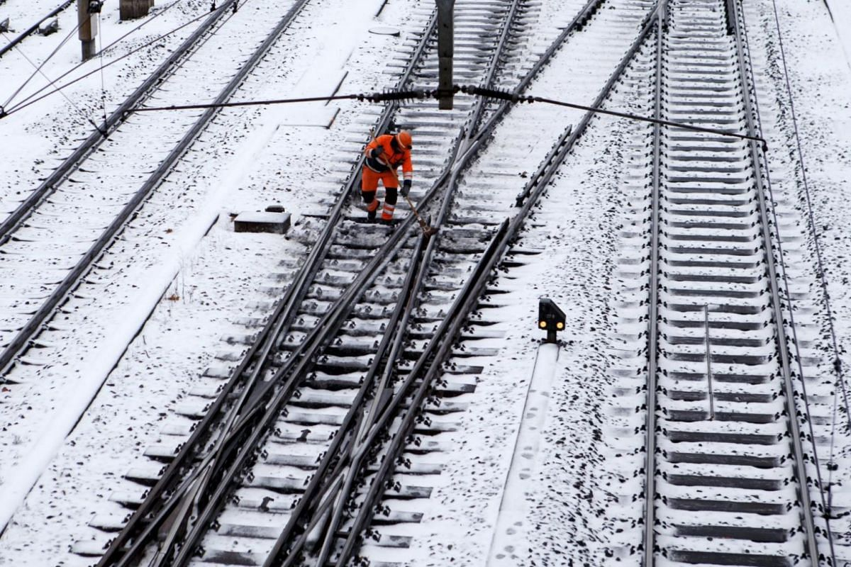 A railroad worker clears the train tracks of ice and snow in Geneva, Switzerland.