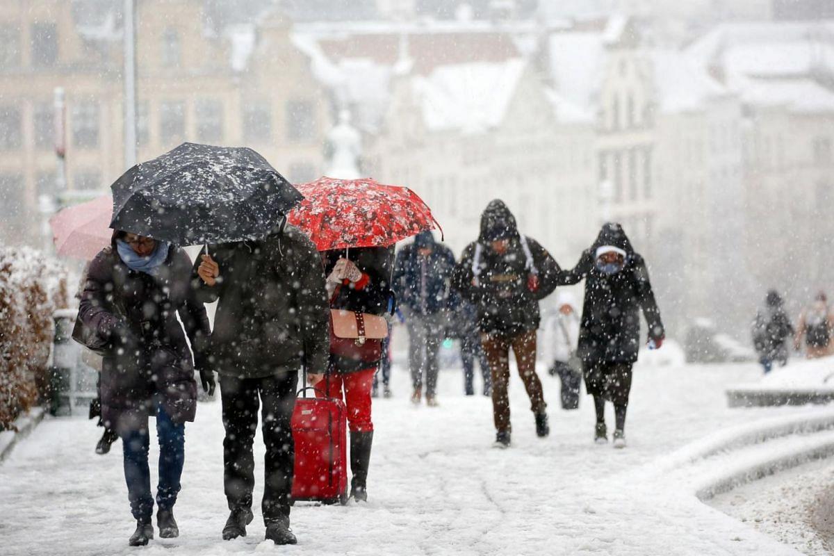 People walking under umbrellas during a snowfall in Brussels, Belgium.