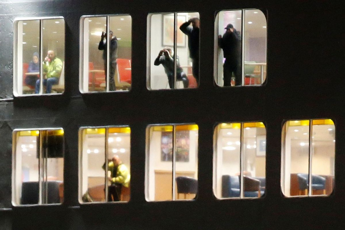 Passengers aboard the P&O ferry Pride of Kent watch rescue operations after the vessel ran aground during bad weather in the port of Calais in northern France, Dec 10, 2017.