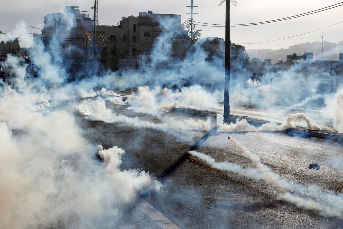 Israeli forces fire gas canisters at Palestinian protesters during a protest in the West Bank city of Bethlehem, Dec 10, 2017.