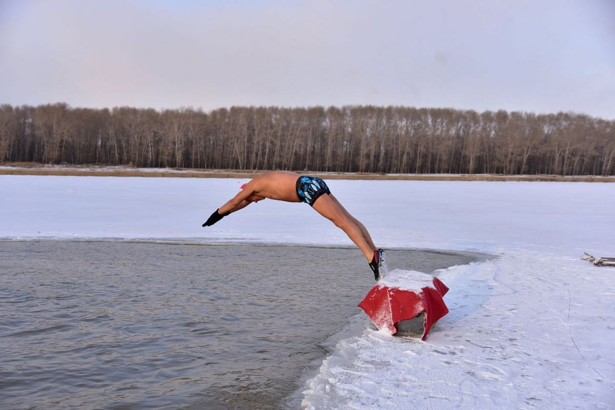 A winter swimmer dives into the icy water of Songhua river in Songyuan, Jilin province, China Dec 11, 2017.