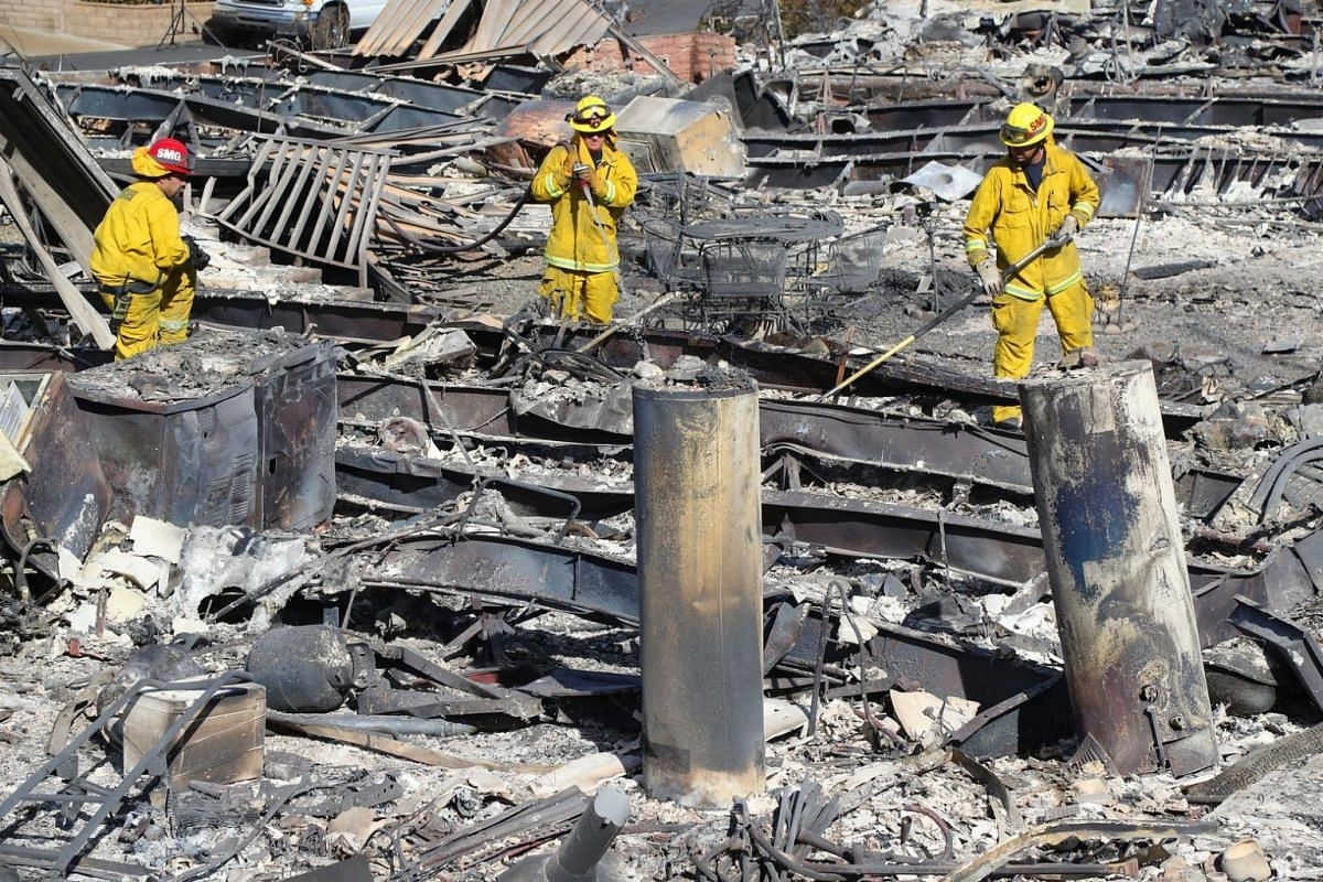 Firefighters check for hot spots at the Rancho Monserate Country Club, a mobile home park, in Fallbrook, California.