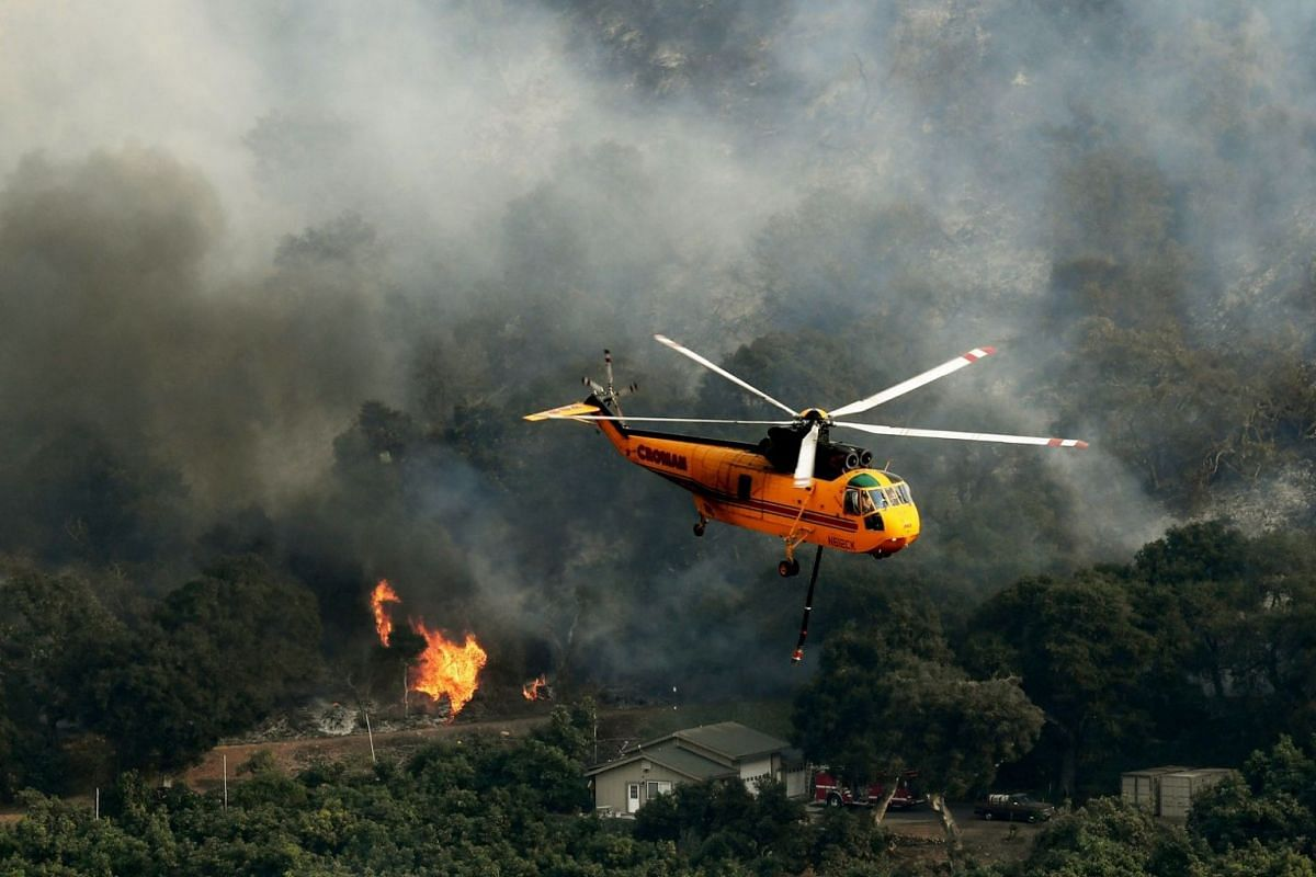 Firefighting helicopters try to save a house from the Thomas wildfire in Carpinteria, California, on Dec 10, 2017.