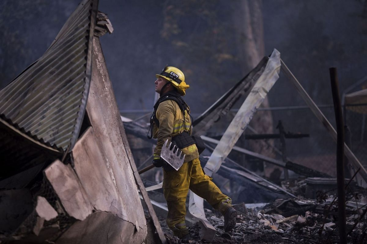 A firefighter looks through the smouldering ruins of a burned house near Casitas Pass Road as the Thomas Fire continues to grow near Carpinteria, California, on Dec 10, 2017.
