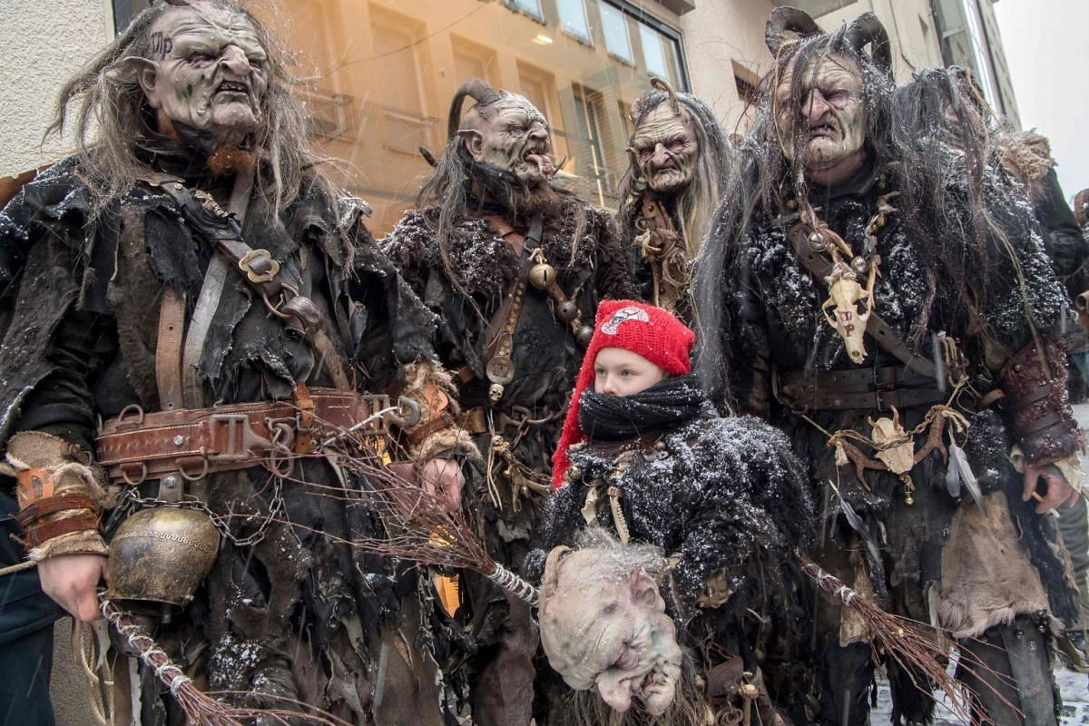 "Six-years old Maxi from Austria stands together with members of his ""Mordred Pass"" association wearing masks featuring the character of ""Krampus"", a half-goat, half-demon figure punishing misbehaving children during the Christmas season, as they prep"