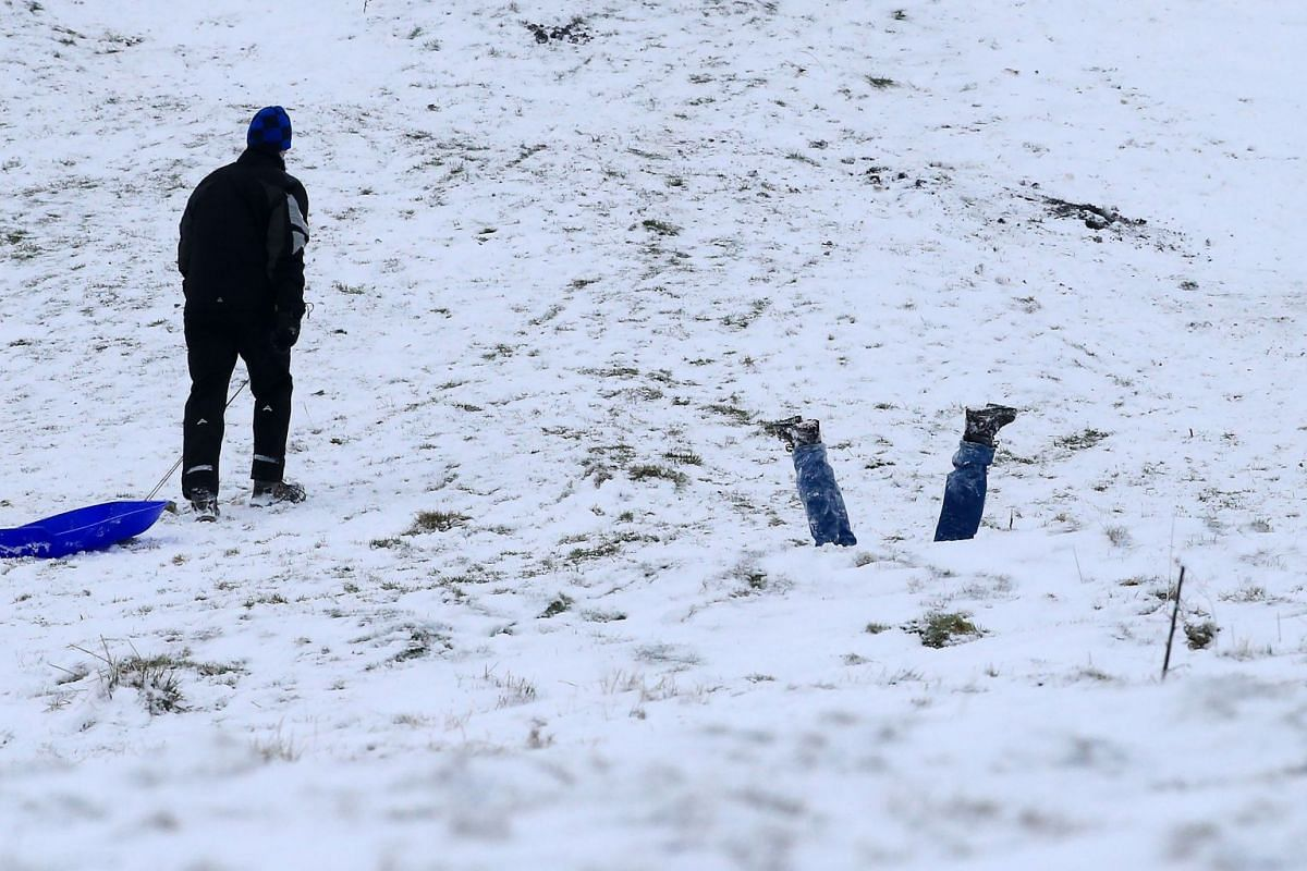Families take to the hills with sledges near Edale in Derbyshire, northern England on Dec 10, 2017. Heavy snow fell across northern and central parts of England and Wales and caused disruption, closing roads and grounding flights at Birmingham airpor