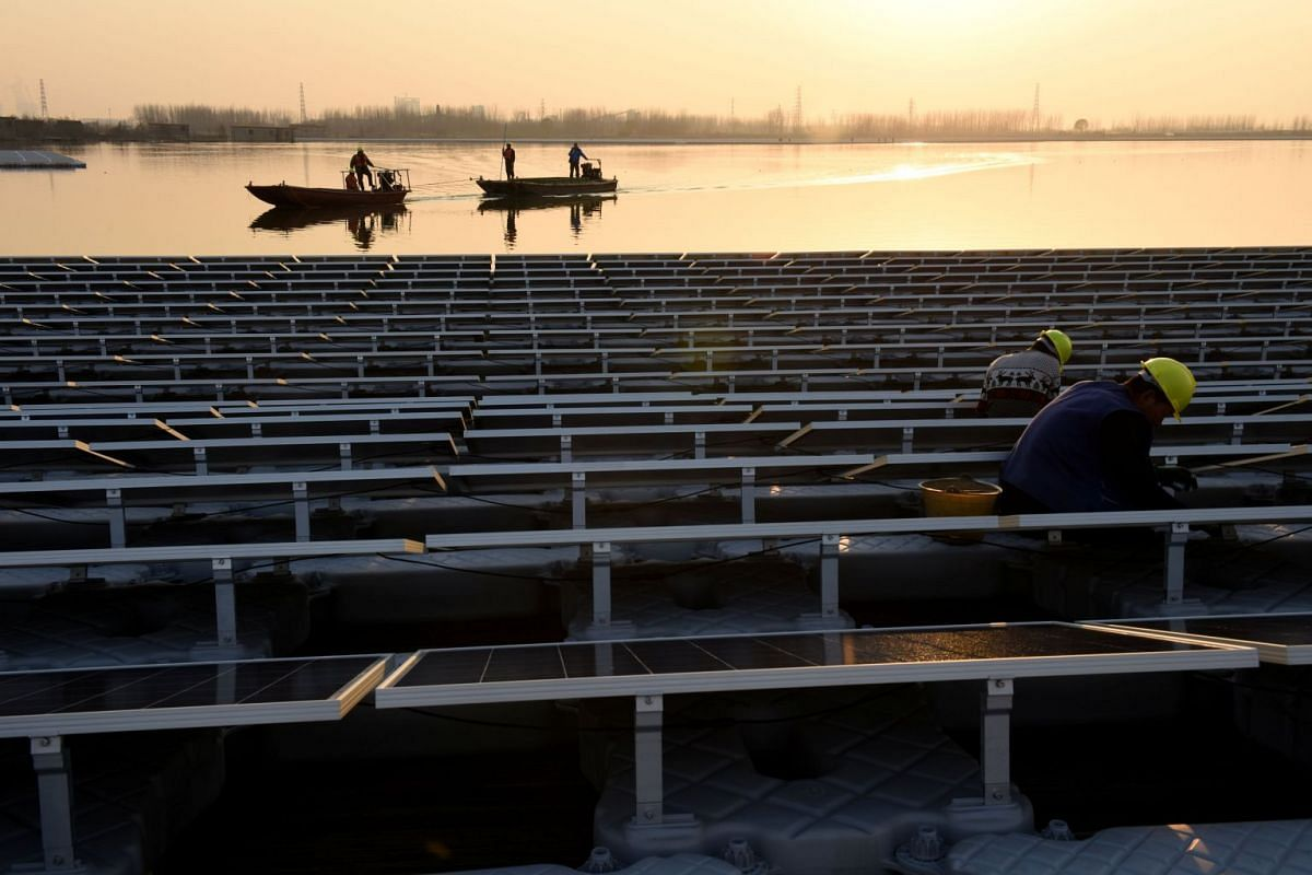 Workers install solar panels at a floating solar plant developed by China's Three Gorges Group, in Huainan, Anhui province, China, on Dec 11, 2017.