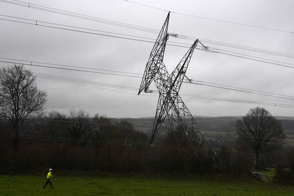 A worker looks on as a damaged very high voltage electrical pylon lies in a field in Montabot, western France, on Dec 11, 2017, after an alleged act of sabotage.