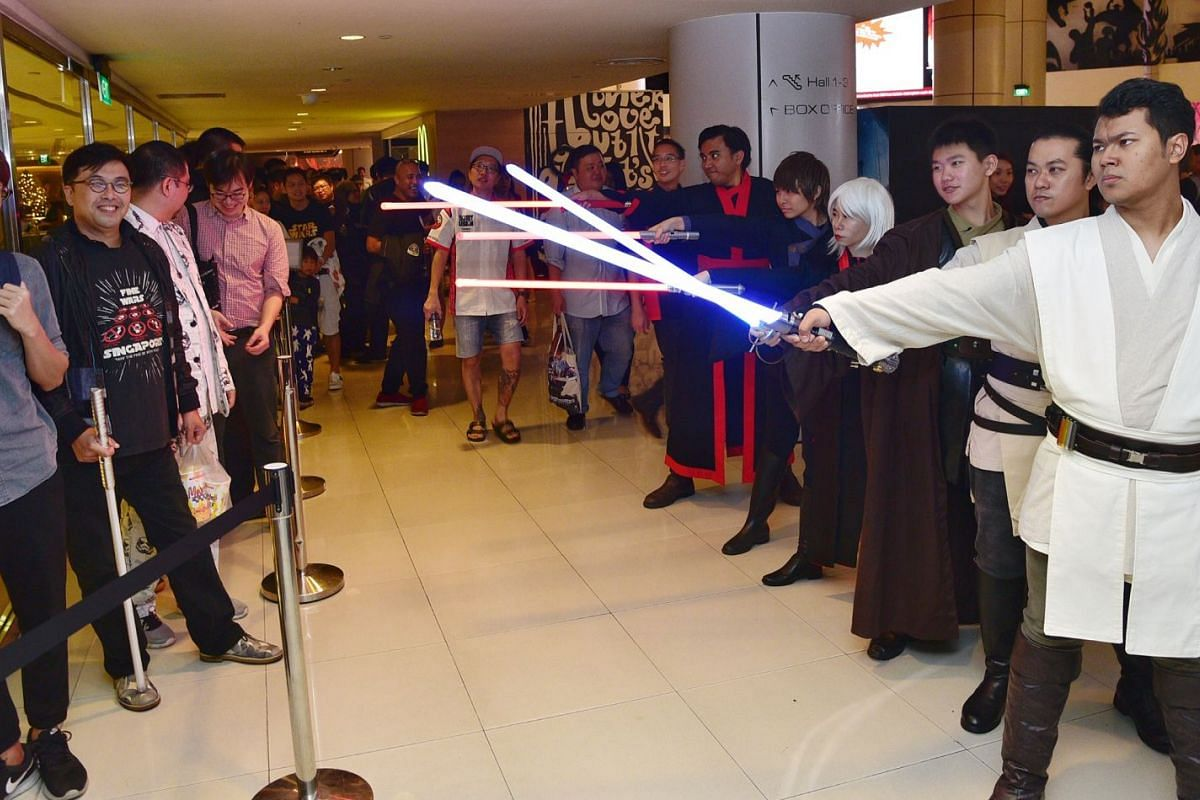 FightSaber Singapore members pointing their sabers at movie-goers.