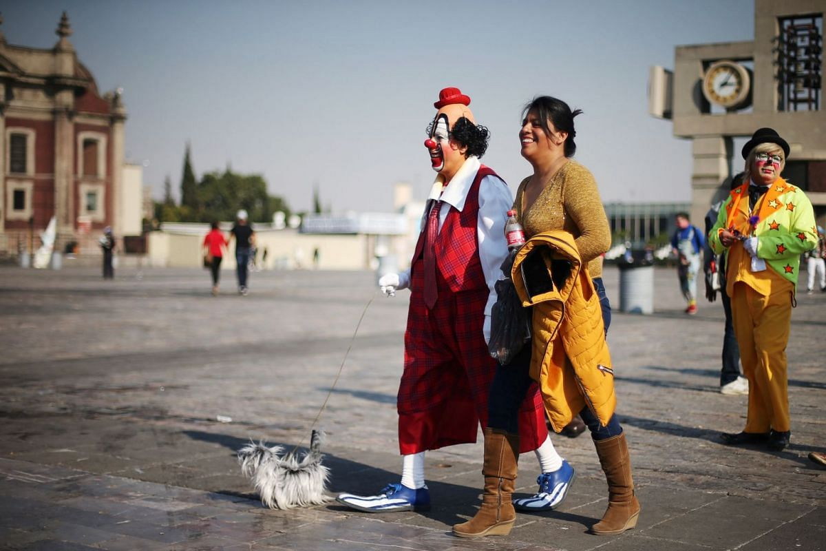 A clown walks with a stuffed toy dog as he pays homage to Mexico's patron saint, Our Lady of Guadalupe at the Basilica of Guadalupe in Mexico City, Mexico, December 13, 2017.