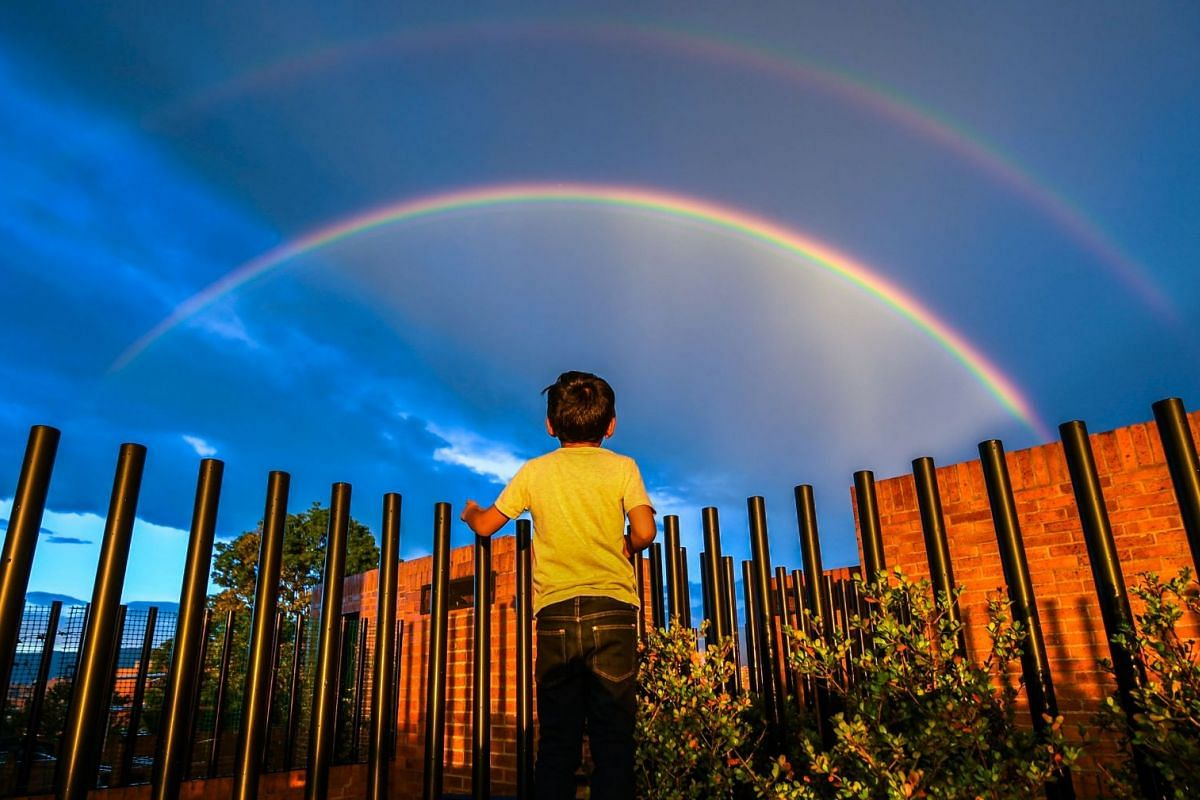 A boy looks at a rainbow during a sunset in Bogota on December 13, 2017.