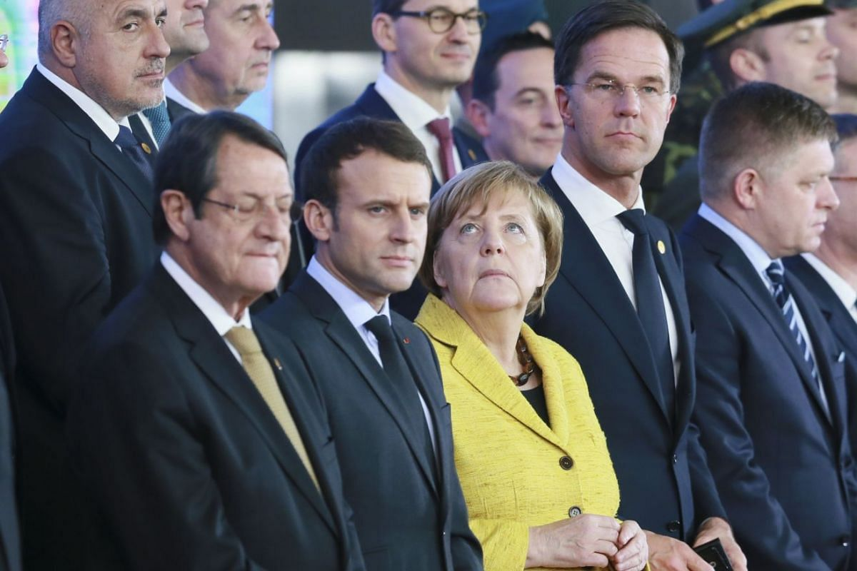 French President Emmanuel Macron (2-L) and German Chancellor Angela Merkel (3-L) with other EU Leaders during a family picture of 24 heads of state members of Defense Permanent Structured Cooperation (PESCO) on the side of during European Council mee