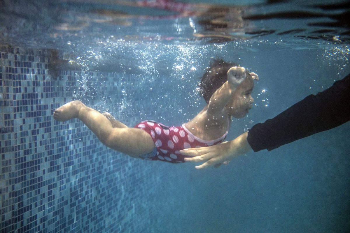 A mother submerges her child during a swimming lesson, at a swimming pool in a school at al-Mokattam, in Cairo, Egypt.