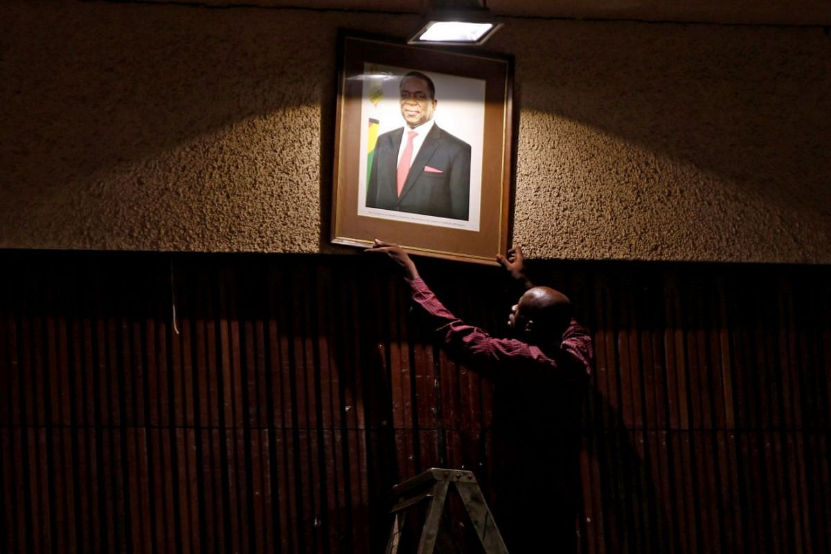 An official puts up a portrait of Zimbabwe's President Emmerson Mnangagwa ahead of a meeting of the ZANU-PF central committee in downtown Harare, Zimbabwe, Dec 14, 2017.