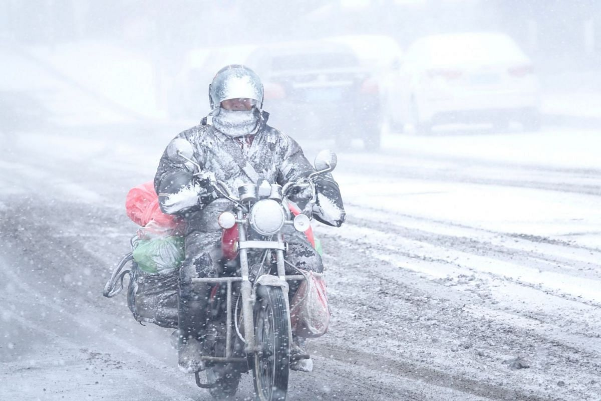A motorcyclist rides amid snow in Dalian, Liaoning province, China, on Dec 16. 2017. PHOTO: REUTERS